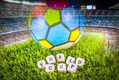 Bola del fútbol en hierba verde y palabras del mundial Imagen de archivo