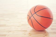 Bola do basquetebol no assoalho de madeira, com profundidade do efeito de campo rendição 3d Fotografia de Stock Royalty Free