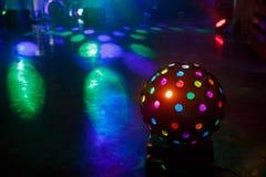 A bola do disco brilha no salão de baile Raios coloridos fotos de stock