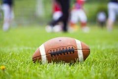 Bola do futebol americano no campo Fotografia de Stock