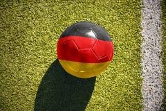 A bola do futebol com a bandeira nacional de Alemanha encontra-se no campo Imagem de Stock