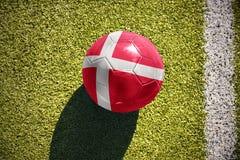 A bola do futebol com a bandeira nacional de Dinamarca encontra-se no campo foto de stock