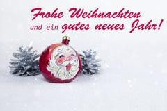 Bola do Natal com o desenho de Santa Claus e de pinhos com texto no ` alemão de Jahr dos neues dos gutes do ein do und de Frohe W Fotos de Stock