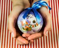 Bola do Natal nas mãos Foto de Stock