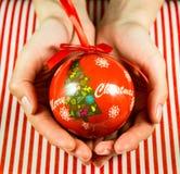 Bola do Natal nas mãos Imagens de Stock Royalty Free