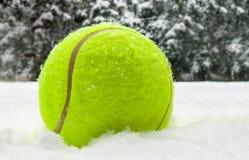 Bola do Natal do tênis na neve no fundo das árvores de Natal, e cartão de esportes de queda dos flocos de neve Feliz Natal e novo foto de stock