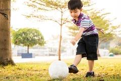 Bola do pontapé do menino no parque na noite imagem de stock royalty free