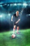 Bola do tiro do jogador de futebol no jogo Imagens de Stock Royalty Free