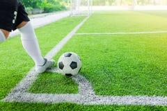A bola do tiro do jogador de futebol no canto fotografia de stock royalty free