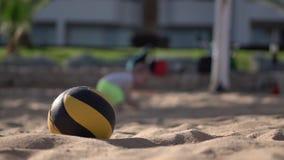 Bola do voleibol no primeiro plano, pouco bebê na caminhada do fundo e queda vídeos de arquivo