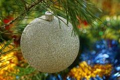 Bola do White Christmas que pendura em um ramo conífero verde Foto de Stock