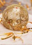 A bola dourada do Natal com vidro da decoração das fitas em uma luz fez malha o lenço, e Year& novo x27; conceito de s Lugar para Fotografia de Stock Royalty Free