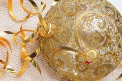 A bola dourada do Natal com vidro da decoração das fitas em uma luz fez malha o lenço, e Year& novo x27; conceito de s Lugar para Imagem de Stock