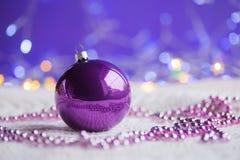 A bola e os grânulos violetas escuros do Natal no branco fizeram malha a tela sobre Fotografia de Stock