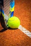Bola e raquete de tênis na corte Fotografia de Stock Royalty Free