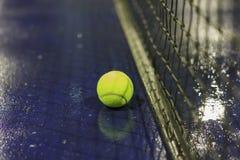 Bola e rede de tênis na terra molhada após chover Foto de Stock