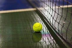Bola e rede de tênis na terra molhada após chover Fotos de Stock Royalty Free