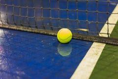 Bola e rede de tênis na terra molhada após chover Imagens de Stock Royalty Free