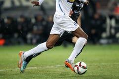 Bola e uns pés de um jogador de futebol Fotografia de Stock