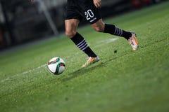 Bola e uns pés de um jogador de futebol Fotos de Stock