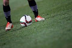 Bola e uns pés de um jogador de futebol Imagens de Stock