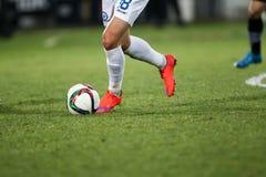 Bola e uns pés de um jogador de futebol Foto de Stock