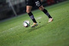 Bola e uns pés de um jogador de futebol Fotografia de Stock Royalty Free