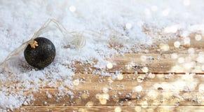Bola en un escritorio de madera, fondo nevoso de la Navidad del bokeh Fotos de archivo