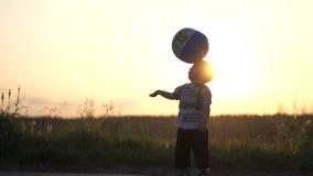 A bola foi jogada para um menino pequeno e bateu-a fora no movimento lento no por do sol video estoque
