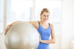 Bola levando da aptidão da mulher bonita no Gym imagem de stock royalty free