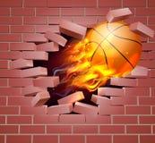 Bola llameante del baloncesto que se rompe a través de la pared de ladrillo Foto de archivo libre de regalías