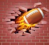 Bola llameante del fútbol americano que se rompe a través de la pared de ladrillo Fotos de archivo libres de regalías