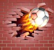 Bola llameante del fútbol del fútbol que se rompe a través de la pared de ladrillo Fotos de archivo libres de regalías