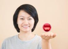Bola mágica roja en la mano asiática de la mujer Fotografía de archivo