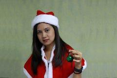 Bola mágica verde en la mano del asiático Santa Girl Dress en fondo verde claro imágenes de archivo libres de regalías