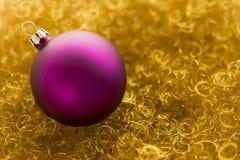 Bola púrpura de la Navidad en brillo del oro Imagen de archivo libre de regalías