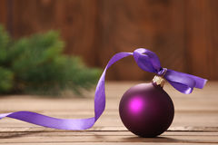 Bola púrpura del juguete de la Navidad con la cinta Fotografía de archivo libre de regalías