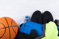 Bola para el baloncesto y ropa de deportes en un bolso azul, en un fondo gris imagen de archivo libre de regalías