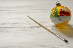 Bola pintada a mano del Año Nuevo con el cepillo en el fondo de madera blanco fotografía de archivo libre de regalías
