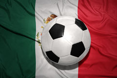 Bola preto e branco do futebol na bandeira nacional de México imagem de stock royalty free