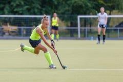 Bola principal femenina joven del jugador de hockey hierba en ataque imagenes de archivo