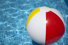 Bola que flutua em uma piscina azul Imagem de Stock Royalty Free