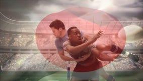 Bola que lanza del jugador del rugbi mientras que siendo abordado abajo por el jugador y la bandera japonesa que agitan en stadi  ilustración del vector