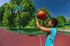 Bola que lanza del muchacho árabe en meta del baloncesto Fotografía de archivo