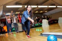 Bola que lanza feliz de la mujer joven en club de los bolos Fotografía de archivo libre de regalías