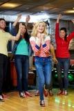 Bola que lanza feliz de la mujer joven en club de los bolos Imagen de archivo libre de regalías
