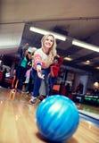 Bola que lanza feliz de la mujer joven en club de los bolos Imagenes de archivo