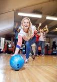Bola que lanza feliz de la mujer joven en club de los bolos Foto de archivo libre de regalías