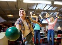 Bola que lanza feliz del hombre joven en club de los bolos Imagen de archivo