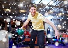 Bola que lanza feliz del hombre joven en club de los bolos Imágenes de archivo libres de regalías